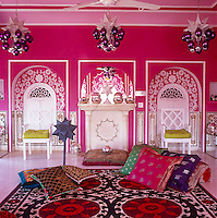 A collection of multicoloured textiles and objects provides interesting counterpoints to the shocking pink walls of the living room