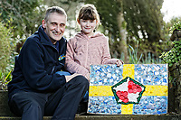 Pictured: Elly Neville with her father Lyn and the flag she created at their home in Pembroke, west Wales, UK. Tuesday 20 February 2018<br /> Re: Seven-year-old Elly Neville who was born despite doctors saying her parents would not be able to have any more children, has raised over £150,000 for the cancer ward that treated her father.<br /> Her parents Lyn and Ann had been told they were unlikely to have more children after he underwent a bone marrow transplant in 2005. <br /> Mr Neville subsequently spent a lot of time on the Ward 10 cancer facility at Withybush Hospital in Haverfordwest, Pembrokeshire.<br /> But four years later they were stunned when his painter and decorator wife Ann fell pregnant again.