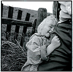 A young girl clings to her fathers leg in front of a levee in the dutch countrysideEurope before the euro.