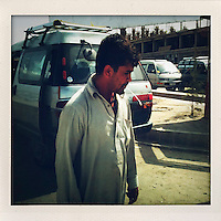 A man walks past a minivan on a Kabul street.
