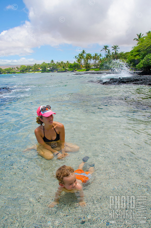 A smiling local mom and her son look at friends just beyond view while playing in a tide pool at a beach in Puako, South Kohala, Big Island.