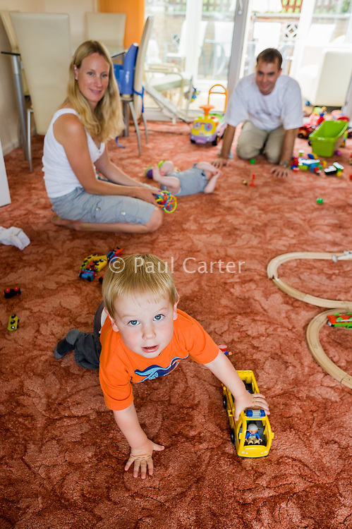 A father and mother play with their two small children, a baby and a toddler, at home on their living room carpet. The toddler is pushing  a toy bus across the carpet...09/07/2011.Hampshire, England, UK