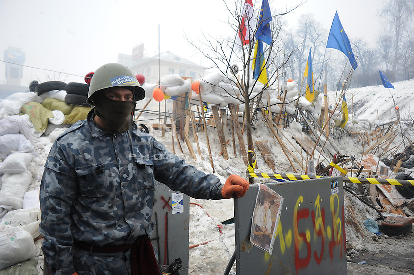 A civil police officer stands guard near the  barricades that have been  restored and rebuilt as complex structures in Maidan square. Kiev,  Ukraine.