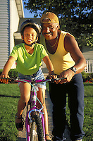 African-american father teaches daughter to ride bicycle