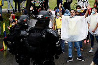 BOGOTA, COLOMBIA - MAY 01 : People confront Police officers as they take part in a protest against Colombian government and the tax reform during the International Workers' Day on May 01, 2021 in Bogota, Colombia. Hundreds of Colombians protest against a tax bill reform plan for the fourth day in a row which aimed to raise some $ 6.3 billion in additional revenue over 10 years for Colombia, which saw GDP fall 6.8 percent in 2020 .(Photo by Leonardo Munoz/VIEWpress)