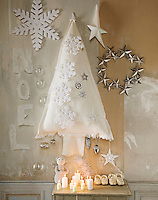 A festive Christmas still life with a handmade fabric Christmas tree and decorations hanging on the wall