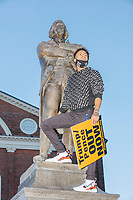"""Azaria Rivera, 23, holds a sign reading """"Trump/Pence Out Now"""" as he stands atop the statue of Samuel Adams outside Faneuil Hall at the end of the 2020 Women's March protest in opposition to the re-election of US president Donald Trump in Boston, Massachusetts, on Sat., Oct. 17, 2020. Azarius Rivera, 23, holds a sign reading """"Trump/Pence Out Now"""" as he stands atop the statue of Samuel Adams outside Faneuil Hall at the end of the 2020 Women's March protest in opposition to the re-election of US president Donald Trump in Boston, Massachusetts, on Sat., Oct. 17, 2020."""