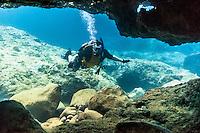 A Caucasian male scuba diver nears an underwater cave at Shark's Cove, North Shore, O'ahu.