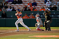 Center fielder Bryce Teodosio (13) of the Clemson Tigers stares into the setting sun as he bats in a game against the Stony Brook Seawolves on Friday, February 21, 2020, at Doug Kingsmore Stadium in Clemson, South Carolina. The Seawolves catcher is John Tuccillo (45). The umpire is Ryan Clark. Clemson won, 2-0. (Tom Priddy/Four Seam Images)