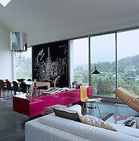 A bright pink contemporary sideboard divides the sitting area from the dining area in this open-plan living space