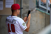 Lansing Lugnuts coach Anthony Phillips (10) takes a photo during a weather delay before a game against the West Michigan Whitecaps on August 24, 2021 at Jackson Field in Lansing, Michigan.  (Mike Janes/Four Seam Images)