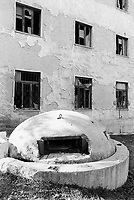 Albania. Province of Vlora. Kukès. A derelict building in the town center with broken windows and a old bunker. Enver Hoxha (1908-1985) decided in 1961 to protect his country from any invaders by investing in a massive fortification (more than a million bunkers were built over the years till 1985).  © 2003 Didier Ruef