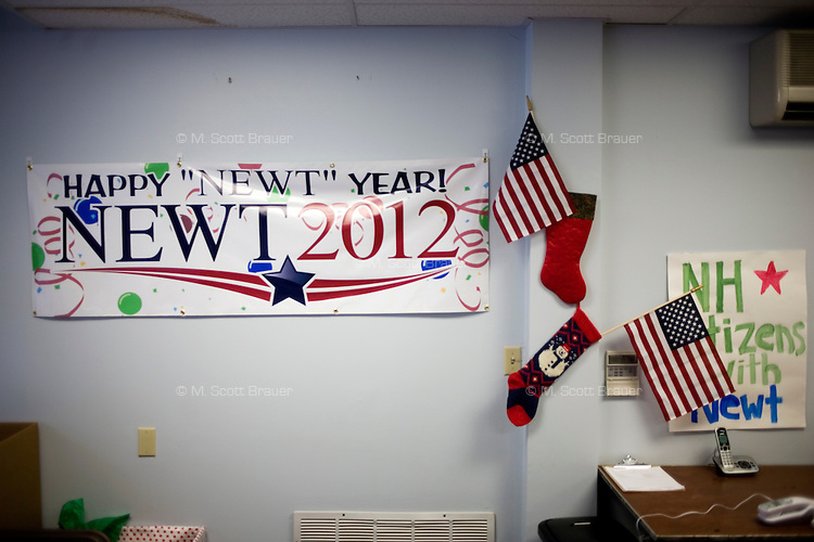 """A banner reading """"Happy Newt Year"""" hangs next to American flags on the wall at the Newt Gingrich New Hampshire campaign headquarters in Manchester, New Hampshire, on Jan. 7, 2012. Gingrich is seeking the 2012 Republican presidential nomination."""