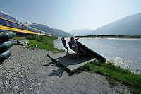 Guides pull a raft out of the water after leading visitors down the Placer River. The Alaska Railroad's Spencer Glacier Whistlestop train gives visitors access to hiking, camping and stunning views.