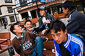 """Youths hang and share a light moment around the city's main clock tower area in downtown Thimphu, Bhutan. Television and the internet have been accessible only since 1999, and were introduced despite widespread fears that their """"controversial"""" content such as fashion shows, western music, wrestling, and pornography, could destroy the kingdom's traditional way of life based on unique Buddhist principles. Sanjit Das/Panos"""