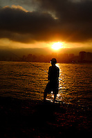 A silhouette of a fisherman casting a line into the sea at sunset overlooking Ipanema beach in Rio de Janeiro