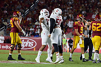 LOS ANGELES, CA - SEPTEMBER 11: Stephen Herron #15 and Dalyn Wade-Perry #50 of the Stanford Cardinal celebrate a tackle by Dalyn Wade-Perry during a game between University of Southern California and Stanford Football at Los Angeles Memorial Coliseum on September 11, 2021 in Los Angeles, California.