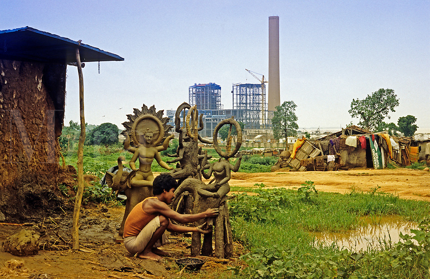 India. Uttar Pradesh. Rihand. Man making clay and straw puja offerings for Hindu ceremonies.  Rihand coal fired power station under construction in the background..