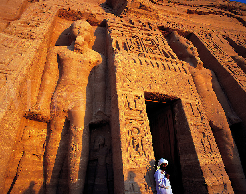 Wide-angle shot of entrance to the shrine to Rameses II at Abu Simbel, with carved frieze and statue, and with guardian standing by doorway; Abu Simbel, southern Egyp
