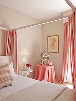 A toning pink tablecloth and curtains add bright splashes of colour in this pretty guest bedroom