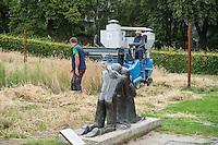 """10 Jahre Roggenernte im ehemaligen Todesstreifen.<br /> Am Donnerstag den 30. Juli 2015 fand auf dem Mauerstreifen an der Kapelle der Versoehnung in der Bernauer Strasse die 10. Roggenernte statt.<br /> Nach biblischem Vorbild wird auf einem Stueck des ehemaligen Todesstreifen Brotgetreide angebaut.<br /> Angeregt durch ein schwedisches Vorbild bei Uppsala entwickelte der Bildhauer und Steinmetz Michael Spengler 2005 die sechs Jahre alte Idee eines Roggenfeldes weiter. Er betonte den starken Bezug des Getreideackers zum Gottesacker.<br /> Thomas Jeutner, Pfarrer der Versoehnungsgemeinde: """"Es steht kein Schild am Rand des Getreidefeldes, das die Kapelle der Versoehnung saeumt. Dass sich hier mitten in der Grossstadt Roggenhalme im Wind wiegen, erklaert sich von selbst: Ein Getreidefeld auf dem ehemaligen Todesfeld. Zeichen des Lebens.""""<br /> Im Bild: Die Skulptur von Josefina da Vasconcellos vor der Kapelle der Versoehnung.<br /> 30.7.2015, Berlin<br /> Copyright: Christian-Ditsch.de<br /> [Inhaltsveraendernde Manipulation des Fotos nur nach ausdruecklicher Genehmigung des Fotografen. Vereinbarungen ueber Abtretung von Persoenlichkeitsrechten/Model Release der abgebildeten Person/Personen liegen nicht vor. NO MODEL RELEASE! Nur fuer Redaktionelle Zwecke. Don't publish without copyright Christian-Ditsch.de, Veroeffentlichung nur mit Fotografennennung, sowie gegen Honorar, MwSt. und Beleg. Konto: I N G - D i B a, IBAN DE58500105175400192269, BIC INGDDEFFXXX, Kontakt: post@christian-ditsch.de<br /> Bei der Bearbeitung der Dateiinformationen darf die Urheberkennzeichnung in den EXIF- und  IPTC-Daten nicht entfernt werden, diese sind in digitalen Medien nach §95c UrhG rechtlich geschuetzt. Der Urhebervermerk wird gemaess §13 UrhG verlangt.]"""