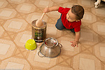 10 month old baby boy hitting coffee can with wooden spoon