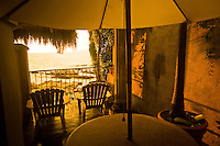 The sun sets over a palapa roof at the Quinta Maria Cortez hotel in Playa Conchas Chinas, Mexico.