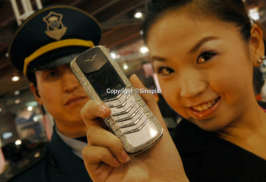 An assistant holds-up a phone encusted with 900 small diamonds worth 200,000 rnb Chinese rnb at the Guangzhou Luxury Goods Fair in China.