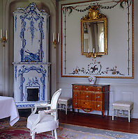 A blue and white tiled stove stands in the corner of this living room which is decorated with hand-painted wall panels