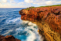 Swirling waters surround the magnificent and rugged red coastline of the Heritage Trail, a hiking trail that offers much to explore in Po'ipu, Kaua'i.