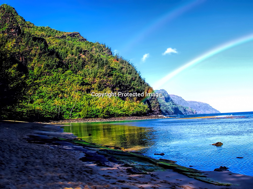Rainbow on early morning Ke'e Beach. Kauai, Hawaii.
