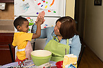 3 year old boy at home with mother in kitchen high five after helping with food preparation