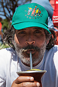 Brasilia, Brazil. Bearded demonstrator from the Via Campesina Movement with a Via Campesina baseball cap drinking Mate tea from a chimarrao.