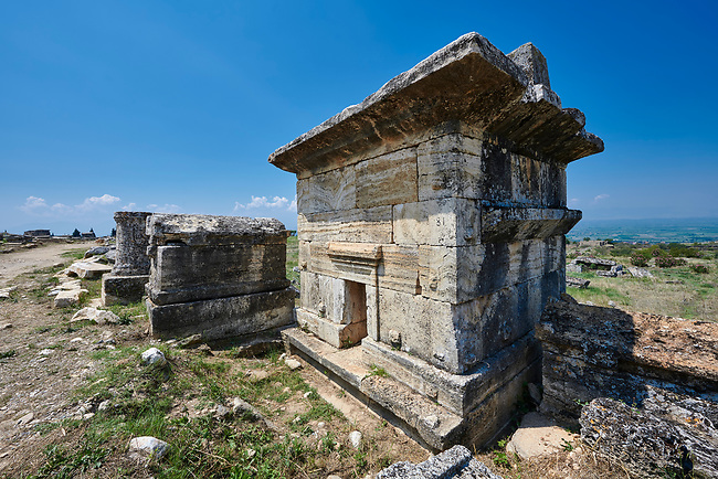 Picture of Tomb  81 of North Necropolis. Hierapolis archaeological site near Pamukkale in Turkey.<br /> <br /> Tomb 81 (2nd - 3rd centuries AD)<br /> The tomb is built on a high platform that compensates for <br /> difference in level of the land behind it. Inside the <br /> chamber are three sepulchre beds, arranged along the walls, an a very deep ossuary. On the roof slabs, which jut out a long way, are two sarcophagi. Two inscriptions beside the door end the inscription on the slab that closed it (now in the museum ) refer to the successive occupants, including Eutyches Pompeios, who left 100 denari to the association of wool washers for the periodic decoration of  <br /> the tomb.