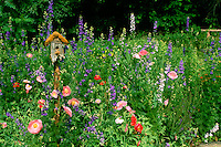 Pastel gaudy garden with moss covered rustic birdhouse, Missouri USA