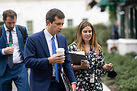 United States Secretary of Transportation Pete Buttigieg speaks with staff members before participating in a television interview at the White House in Washington, DC, October 13, 2021. Credit: Chris Kleponis / Pool via CNP /MediaPunch