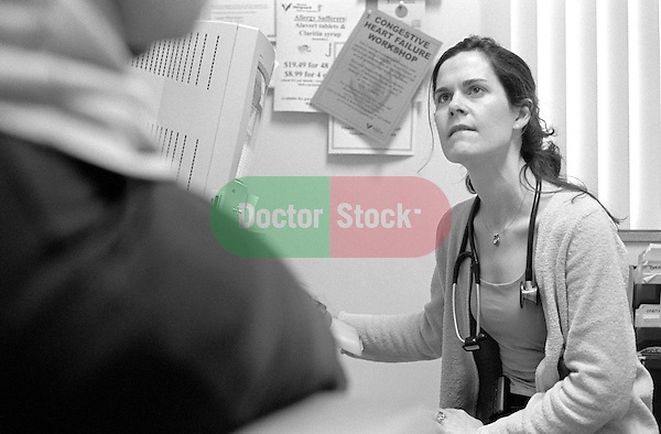Young female internal medicine resident physician looking up to patient partially off camera sitting on examination table