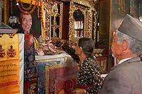 Bodhnath, Nepal.  Visitors to the Tsamchen Gompa (Buddhist Monastery) Making Money Offerings.