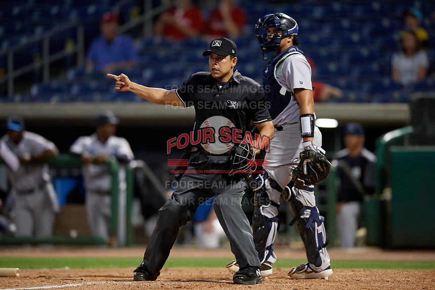Umpire Jhonatan Biarreta signals fair ball in front of catcher  Jason Lopez during a Florida State League game between the Tampa Tarpons and Clearwater Threshers on April 18, 2019 at Spectrum Field in Clearwater, Florida.  Clearwater defeated Tampa 10-3.  (Mike Janes/Four Seam Images)