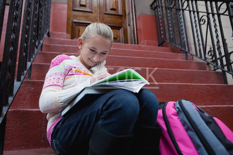 USA, New York State, New York City, Girl (10-11) doing homework while sitting on steps