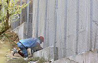 "Pictured: A migrant sneaks in through the fence to get belongings at Moria camp on Lesbos island.<br /> Re: Up to 4,000 migrants were evacuated from the Moria camp on the Greek island of Lesbos after a large fire destroyed tents and prefabricated homes.<br /> No injuries have been reported, and some migrants have now been allowed to return to the camp.<br /> Police are investigating whether the fire was deliberate, but an aid worker said it started after a food dispute.<br /> There are some 5,600 refugees currently in Lesbos, according to the UN, but the island only has capacity for 3,600.<br /> The fire destroyed 30% of the camp, according to Aris Vlashopoulos, an aid worker with the Swiss charity SAO.<br /> ""People are returning to the camp now as I can see. But the biggest number of the refugees are already on the streets, sleeping outside,"" he added."