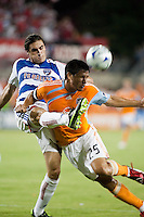 FC Dallas defender George John (14) clears the ball away from Houston Dynamo forward Brian Ching (25).  Houston Dynamo defeated FC Dallas 1-0 at Robertson Stadium in Houston, TX on May 9, 2009