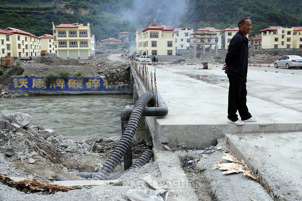 A man stands on a bridge that leads to newly built homes, built to rehouse local Tibetans displaced by the Maoergai Dam, in the Tibetan region of Aba.  South-east Tibetan Plateau, in Sichuan Province, western China.