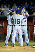 Jared Young (16) of the South Bend Cubs is greeted at home plate by teammates Chris Singleton (left) and Chris Carrier (13) after hitting a 3-run home run against the Lansing Lugnuts at Cooley Law School Stadium on June 15, 2018 in Lansing, Michigan. The Lugnuts defeated the Cubs 6-4.  (Brian Westerholt/Four Seam Images)