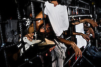 """A Mara gang member looks through the bars in a cell at the detention center in San Salvador, El Salvador, 20 February 2014. Although the country's two major gangs reached a truce in 2012, the police holding cells currently house more than 3000 inmates, five times more than the official built capacity. Partly because the ordinary Mara gang members did not break with their criminal activities (extortion, street-level distribution of drugs, etc.), partly because Salvadorean police still applies controversial anti-gang law which allows to detain almost anyone for """"suspicion of gang membership"""". Accused young men are held in police detention centers where up to 25 inmates may share a cell of five-by-five metres. Here, in the dark overcrowded cages, under harsh and life-threatening conditions, suspected gang members wait long months, sometimes years, for trial or for to be transported to a regular prison."""