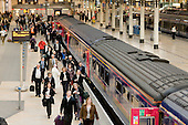 Passengers board a train from a platform at Paddington station