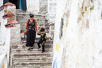 A mother and child walk down stairs inside Ganden monastery in Tibet. The monastery is one of the most important in the region and sits on top of a mountain near Lhasa at an altitude over approximately 4,300m. Pilgrims steadily stream through the monastery throughout the day, exploring the narrow alleyways that criss cross the monastery's interior.