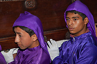 Antigua, Guatemala.  Two Young Men, Cucuruchos, Carrying a Float (Anda) in a Religious Procession during Holy Week, La Semana Santa.