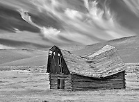 Fallen down barn with wispy clouds. Montana