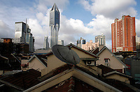 New skyscrapers tower above an old residential neighborhood in downtown Shanghai, China..